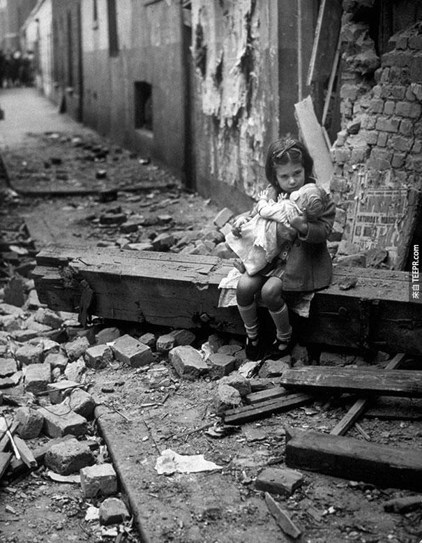 小女孩跟他的玩偶坐在被炸毀的家中 - 倫敦 1940