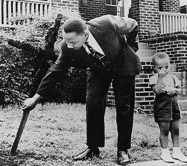 馬丁·路德·金跟兒子在他們的前院把燒焦的十字架移除 - 1960