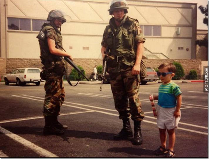 一名小朋友在一些國民警衛隊成員旁邊拍照 (洛杉磯,美國 1992)