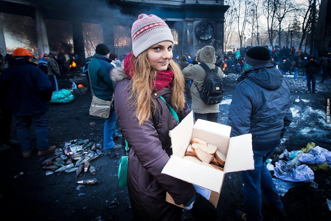 一名每少女把三明治送給示威的群眾 (烏克蘭 2013)