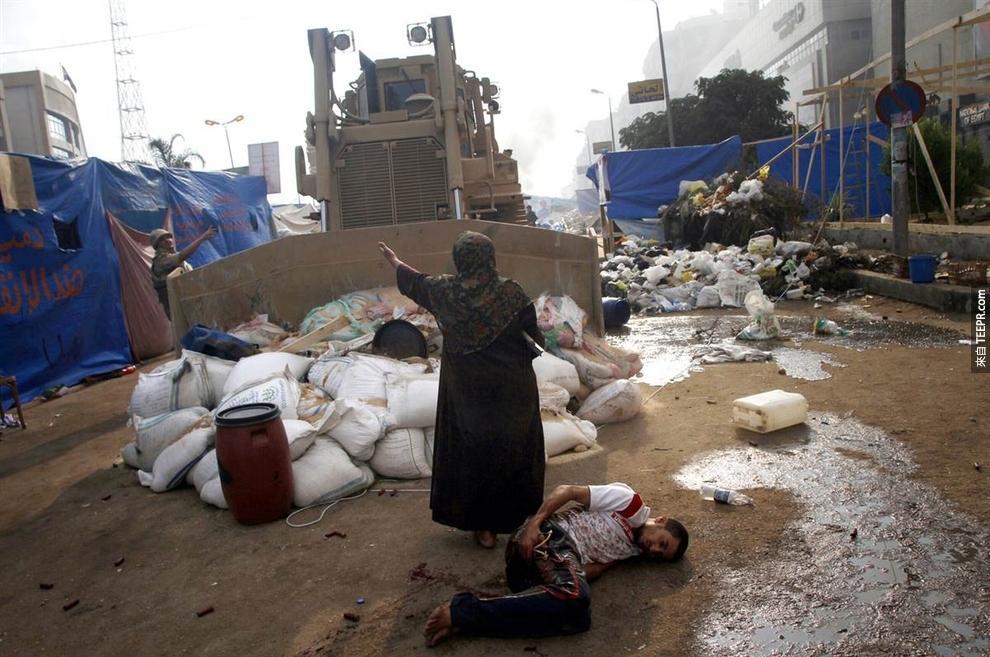 一名女子檔在一台軍用的推土機,保護著一名受傷的示威者 (埃及2013)