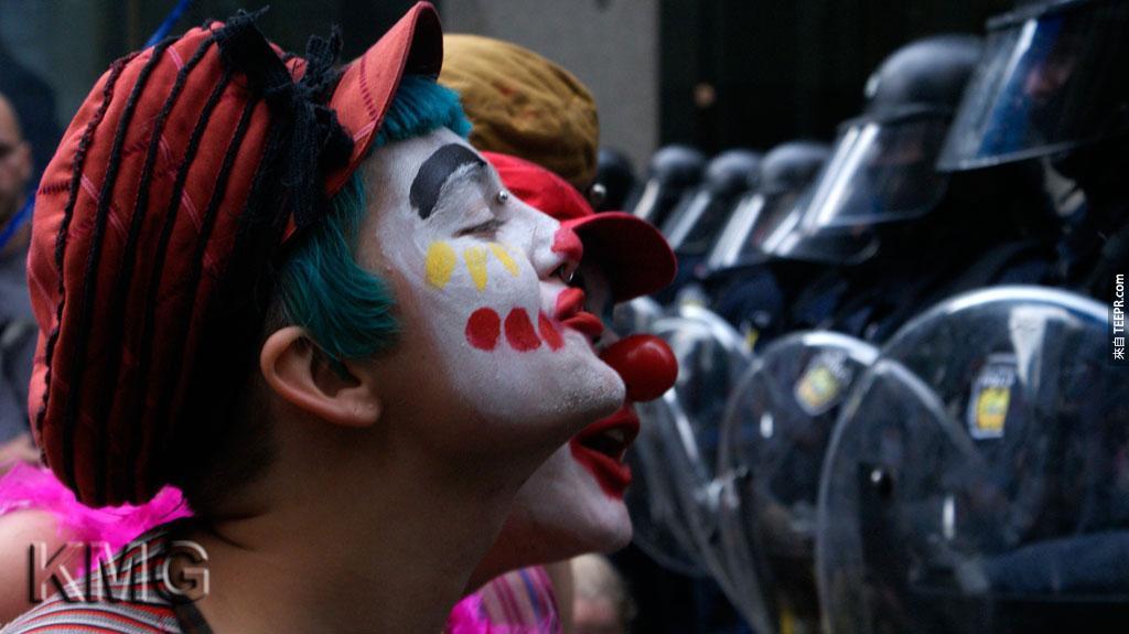一些穿成小丑的示威民眾提供娛樂服務給站守G20的侍衛 (多倫多,加拿大 2010)