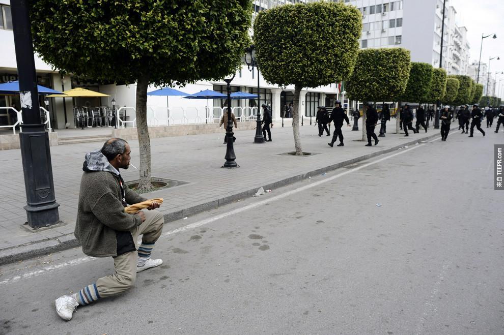 一名突尼西亞的民眾拿著一個法國麵包,敵檔著警察的猛攻 (突尼西亞 2010)。