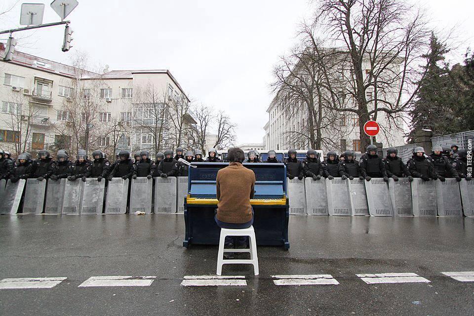一名男子為了警察彈奏鋼琴 (基輔,烏克蘭 2013)