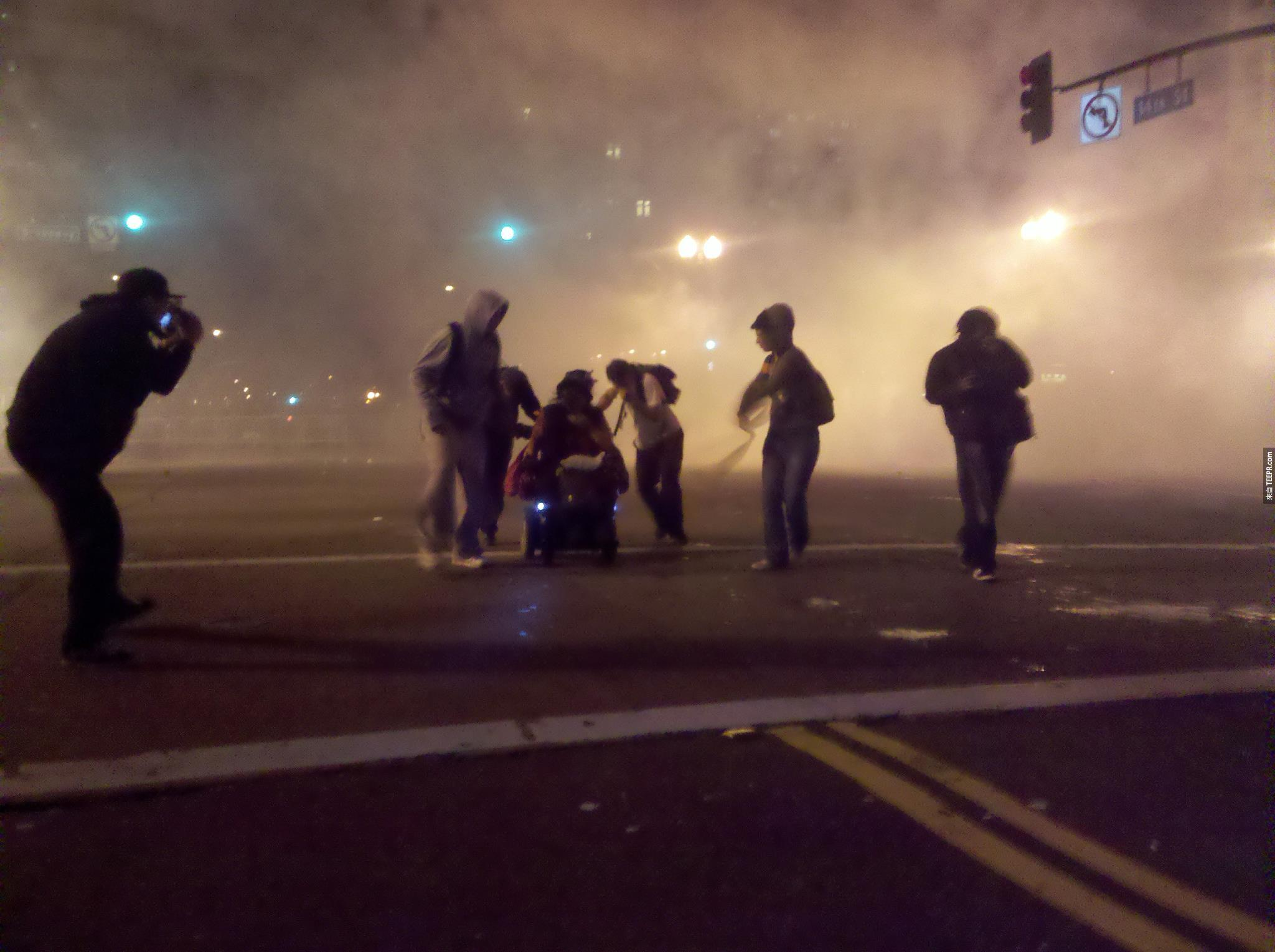 """""""佔領華爾街""""時,示威民眾帶著一名殘障坐在輪椅的女士逃離催淚瓦斯 (奧克蘭,美國 2011)。"""