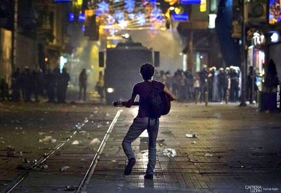 一名土耳其的示威著彈奏吉他給警察聽 (土耳其 2011)。