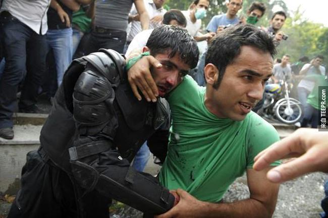 一位平民保護著一名被暴亂示威的群眾打傷的警察 (伊朗德黑蘭 2009)。