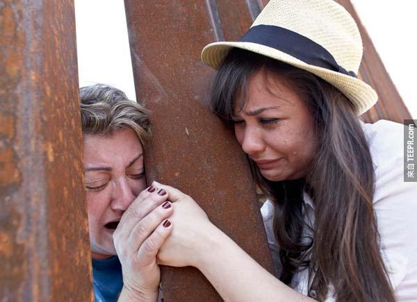 在亞利桑那州的邊境柵欄,一位女孩緊抓著她六年前被驅逐至墨西哥的母親的手。