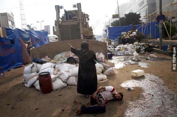 在埃及開羅,這位勇敢的女人不顧自身安危,試圖全力阻止正在運行的軍事推土機只為了搶救一名受傷的男子。