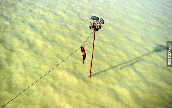 一位在印度的年輕男孩試圖逃避洪水而被迫懸吊在電纜線上。