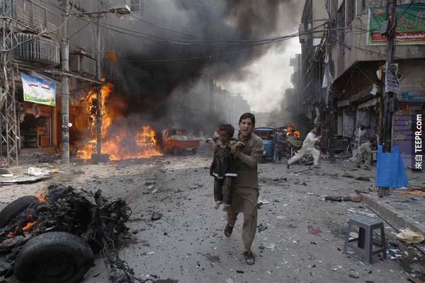 巴基斯坦北部發生了汽車爆炸案,一名巴基斯坦男子抱著一名小孩逃離事故現場。