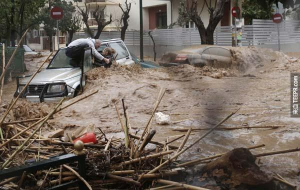 在二月的希臘雅典洪水災害道路現場,一位英勇的男士救出因為洪水而被卡在車內的女士。