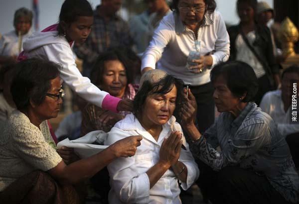 這位女士在柬埔寨國王葬禮之前,正在進行剃髮以象徵哀悼的情緒。