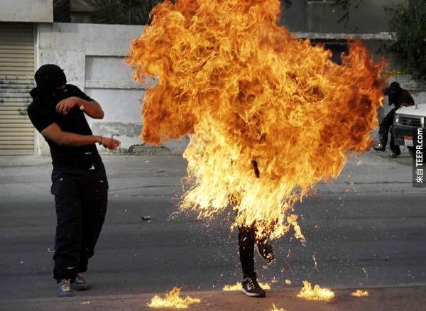 在巴林( Bahraini )的示威者正要扔出汽油彈的同時卻爆炸在他的手中,身體完全被熊熊無情大火吞噬。