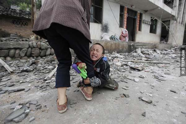在中國四川地震餘波中,一名小男孩緊緊抓住母親的大腿哭泣。