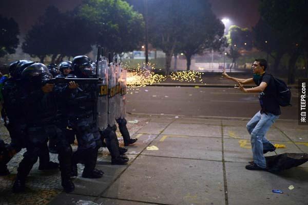 在巴西里約熱內盧(Rio de Janiero)爆發抗議衝突後, 一名示威遊行者被警察用橡皮子彈攻擊。
