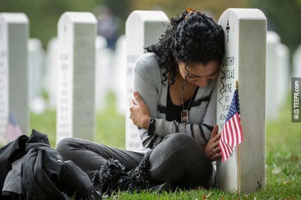 阿靈頓國家公墓一角,這位寡婦悲傷著緊靠在阿富汗戰爭而死去的丈夫墓碑前。