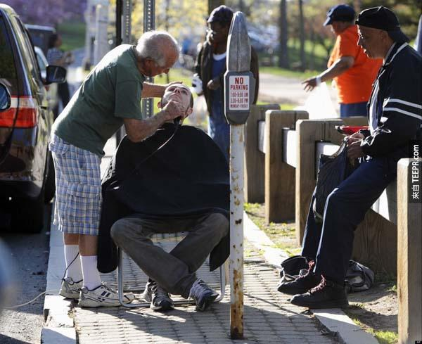 23.) 這位82歲的理髮師拿著剪刀在停車場幫人們剃鬍子。