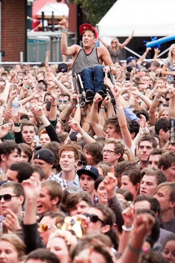 25.) 群眾將一位坐輪椅的年輕小夥子,抬起來歡呼。