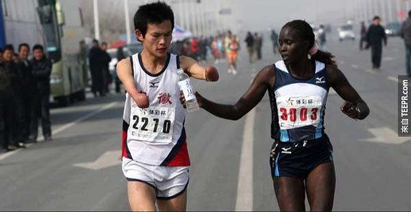 31.) 一位世界級的馬拉松跑者慢下腳步,幫助一位身障人士喝水。