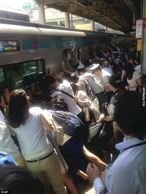 33.) 在火車站裡,很多人正在幫忙推火車,拯救一個掉到軌道上的人。