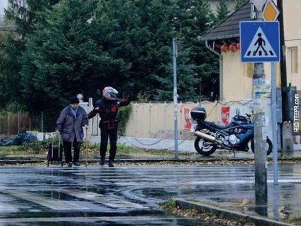 34.) 這位機車騎士將他的車靠在路邊,幫助一位年長的婆婆過馬路。