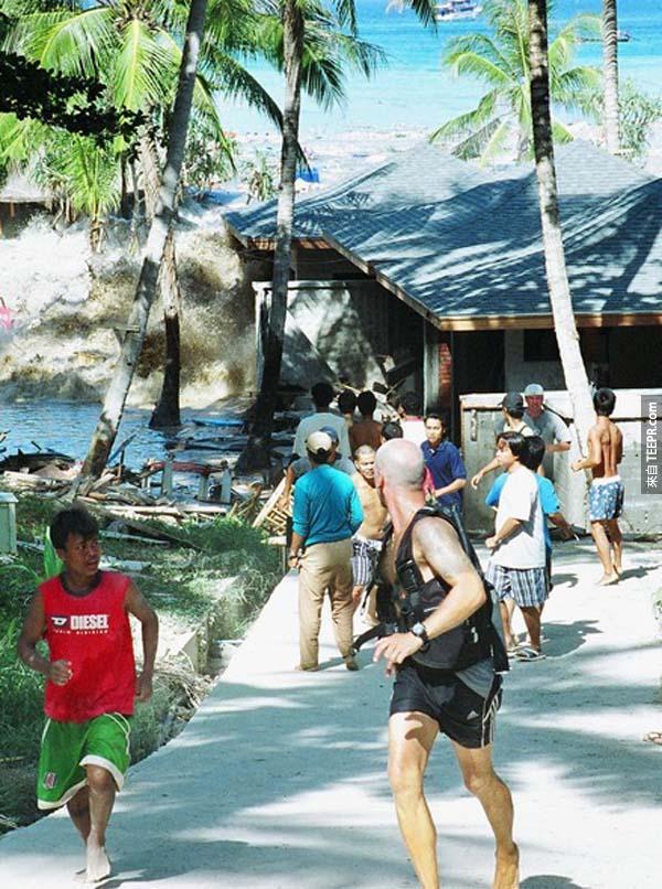 13.)2004年海嘯襲擊泰國,遊客與當地人在神色倉皇地逃跑。