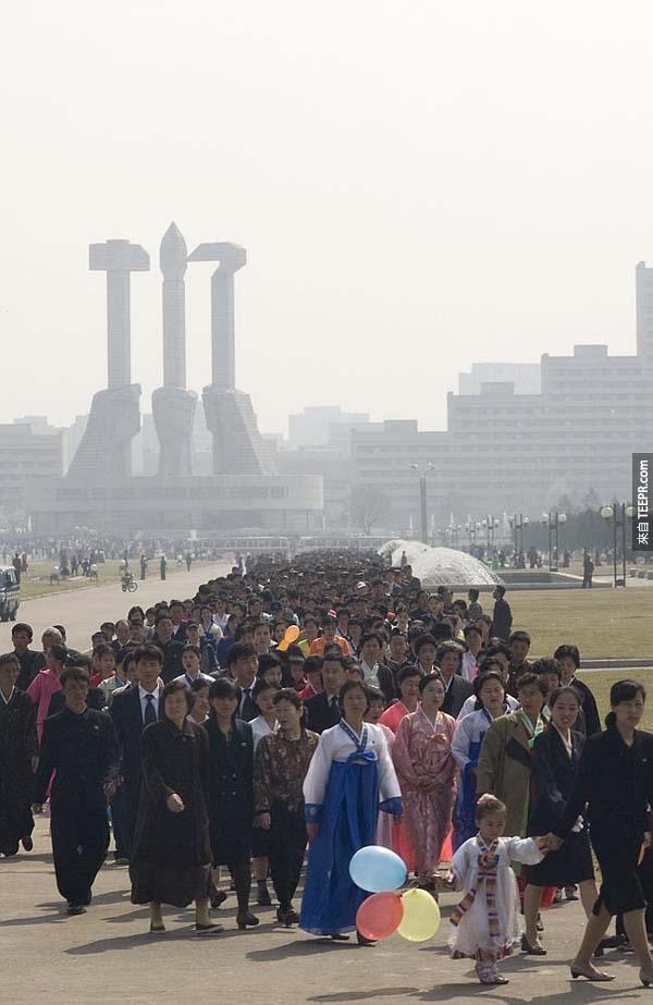 在金正日花节(Kimjongilia festival)当天,数千名北韩人必须列队去缅怀金正日的纪念碑。