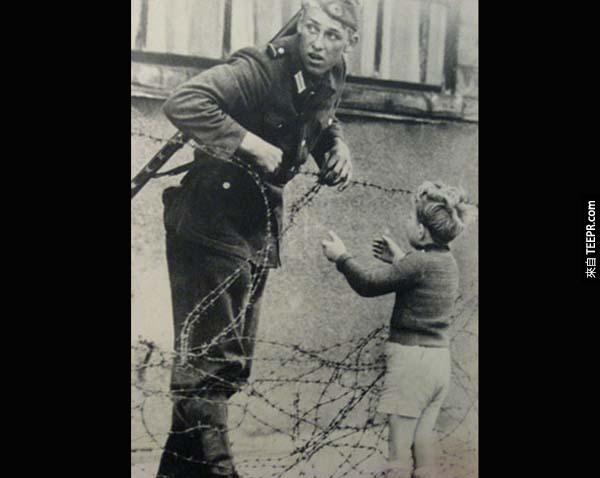 4.) 柏林圍牆的拯救: 這位來自東德的軍人知道他不應該讓這名孩童跨越柏林圍牆,但孩童與他的父母走散了。這位士兵還是把鐵絲撩起來,讓孩童過去,但他非常警戒,四處觀看是否有人看見。(那拍照的人呢?)