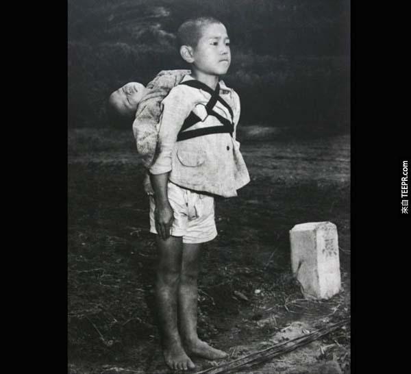 10.) 長崎市(Nagasaki)兄弟檔: 這張照片攝於空襲發生後不久。照片中年紀較小的孩童已經死了,年紀較大的這位是他的哥哥。他正帶著他的弟弟前往火葬場,可以看見他的眼神是如此地堅強,忍著快要低下來得淚水。即便他已經失去全世界,他仍要光榮地送弟弟最後一程。