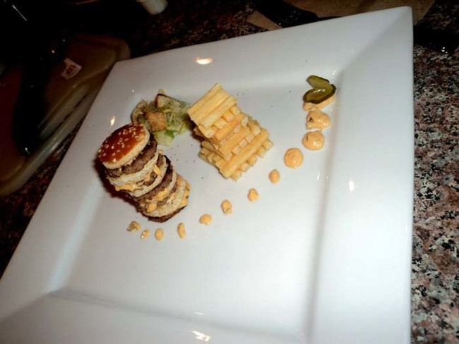 The first entry: 5 times cheeseburger with a potato tower, salad with sesame seed bun croutons & mac sauce garnish.