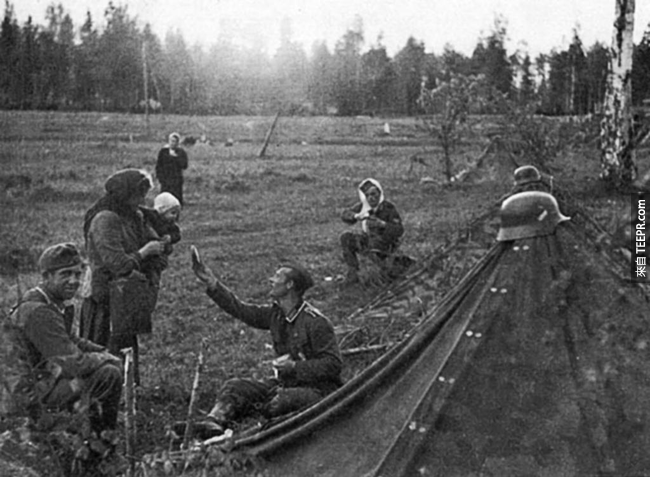16.) 一名德國軍人將他的食物分給當地的俄羅斯媽媽。