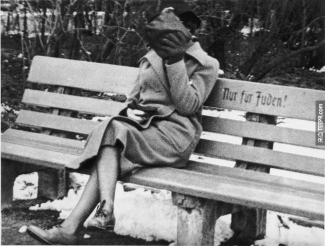 4.) 一位猶太女士在奧地利的長椅上坐著,上面寫著「猶太人區」,1938。