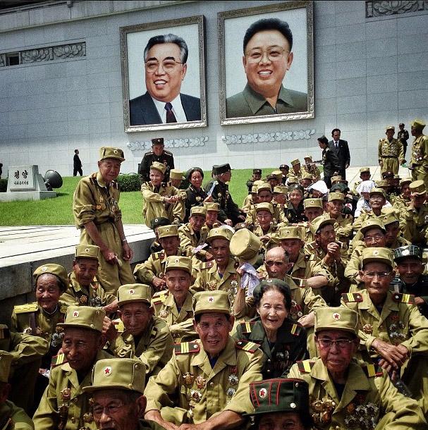 朝鮮戰爭的退伍軍人們坐在領導人的肖像前。
