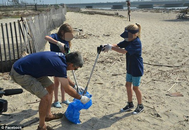 Mr El-Erian described his work-life balance being 'out of whack' - so he resigned from PIMCO to spend more time with his wife and daughter. He is pictured in 2011 helping clean up the Orange County coastline with a volunteers as part of PIMCO project