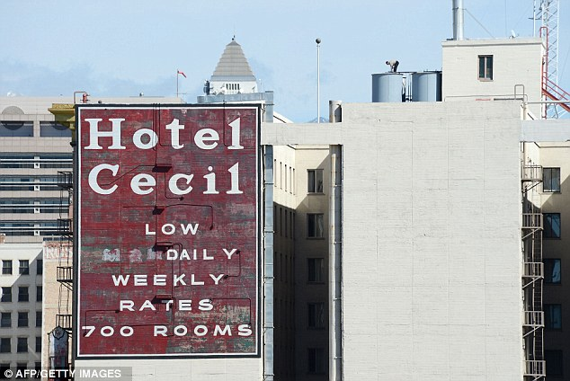 A worker stands on a water tank on the roof of the Hotel Cecil where the 21-year-old was found