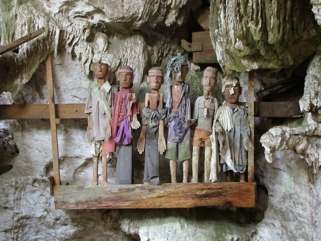 """Then a """"Tau Tau,"""" a wooden effigy of the deceased, is placed on a cave wall along with those of their ancestors."""