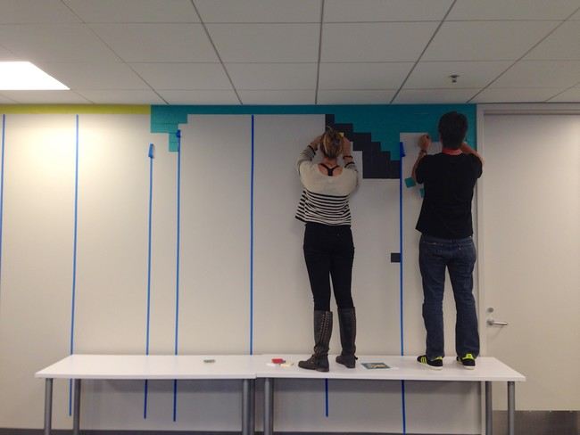 The colleagues gathered on a Saturday for the installation. The borders were marked out with tape, and the application of the Post-Its began.