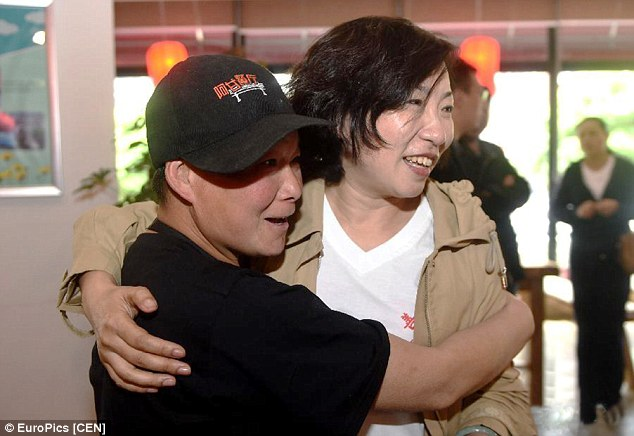 A waiter with learning difficulties is hugging his relative in the restaurant