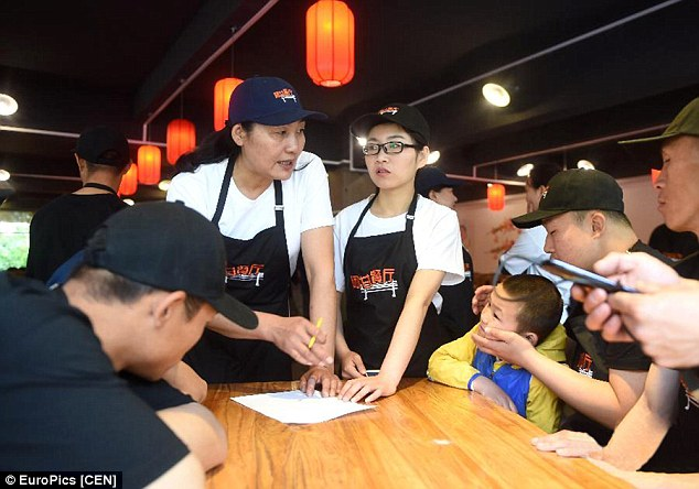 Impaired workers, who wear black uniform, are offered work after they pass the training provided by Hu