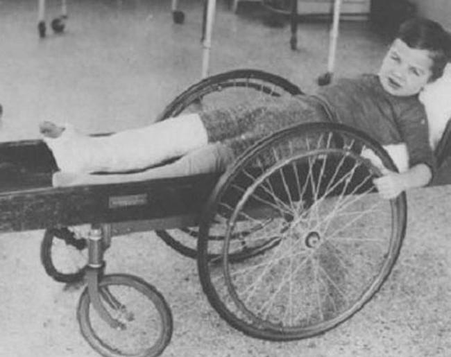 "This injured boy is wheeling around in an ""invalid cart."""