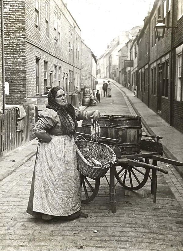 Woman selling fish from a barrel on the streets of London, 1910.