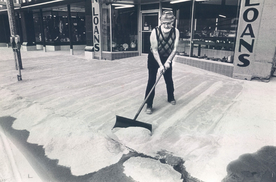 Mike Clinton shovelling volcanic ash off the sidewalk from Mount St. Helens. The volcano in Yakima, Washington erupted on May 18, 1920.