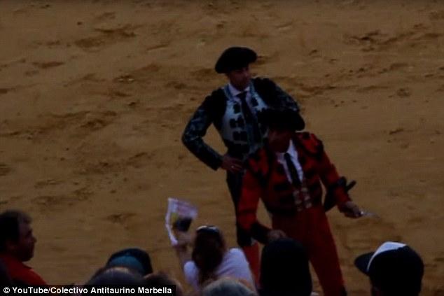當鬥牛士要給這頭鬥牛最後致命一擊時,這名女觀眾看到牛的神情不對勁後就立刻衝出去保護他。