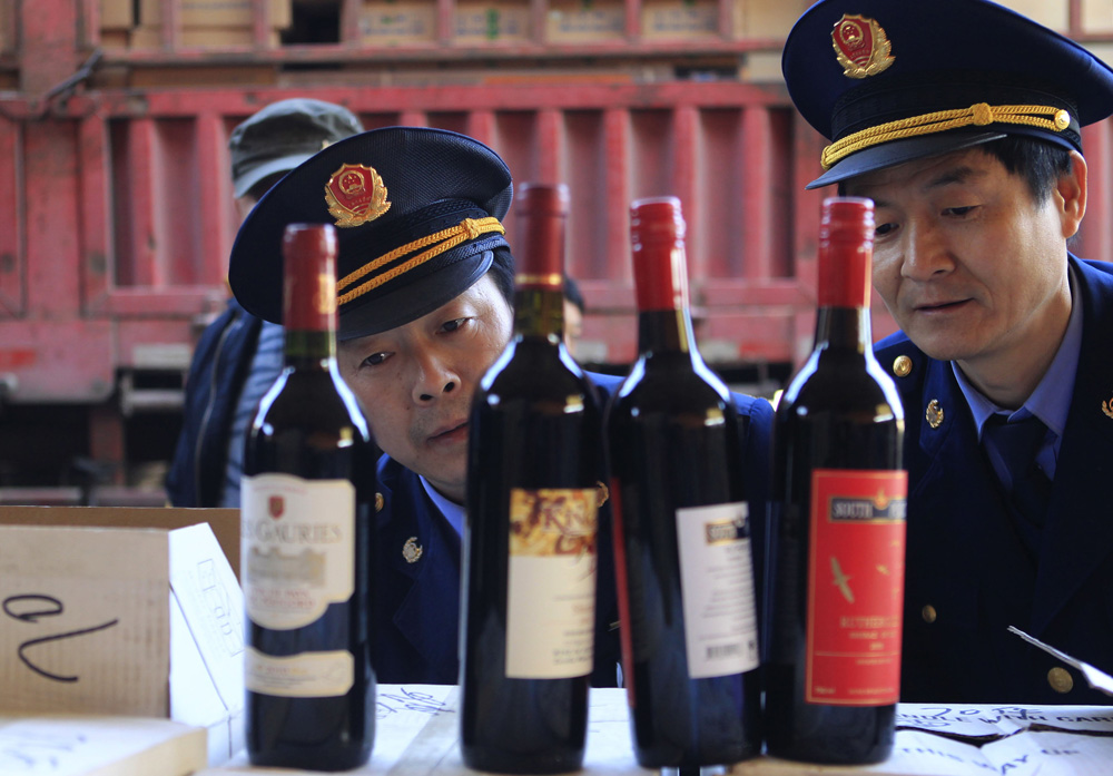 Police officers check bottles of confiscated fake wines before destroying them in Xi'an