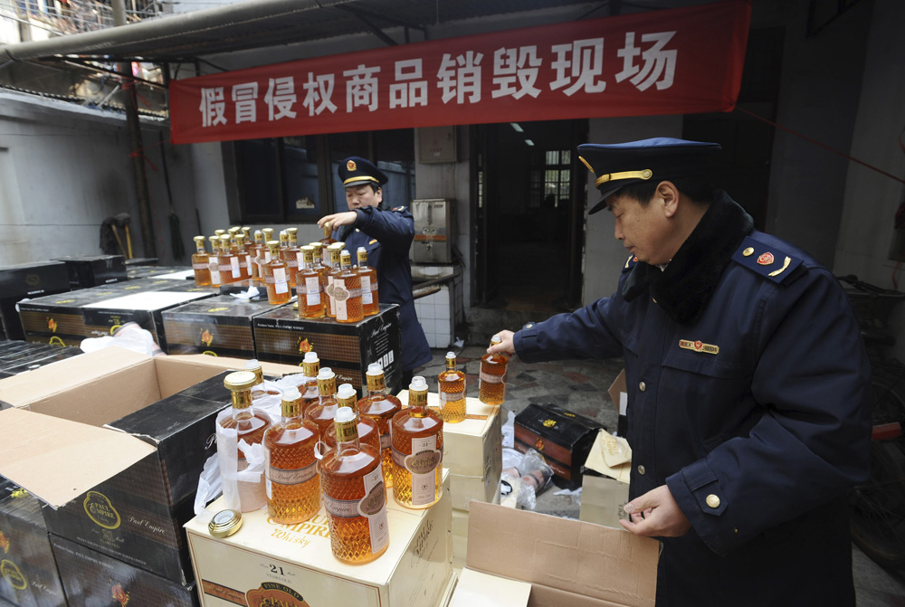 Commercial law enforcement personnel examine bottles of confiscated fake whisky before pouring it into sewage during a massive destruction campaign of fake products in Wuhan