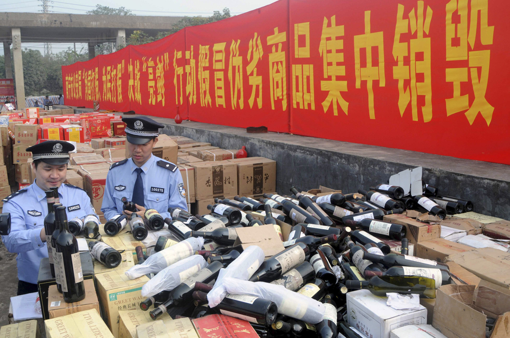Police officers check bottles of confiscated fake wines before destroying them in Nanning