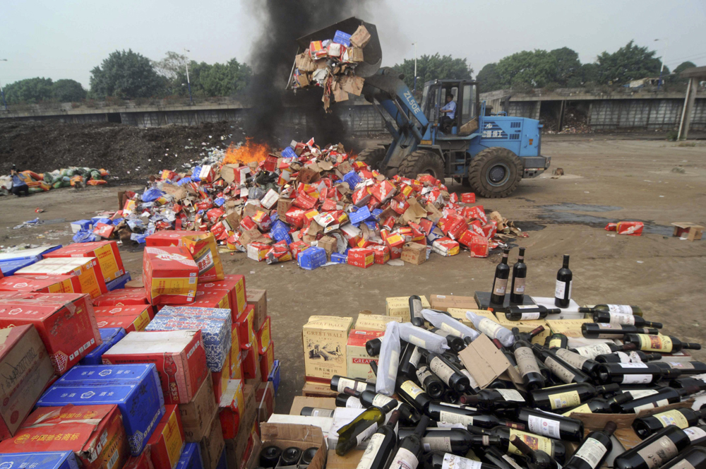 Confiscated bottles of fake wines are destroyed by the police in Nanning