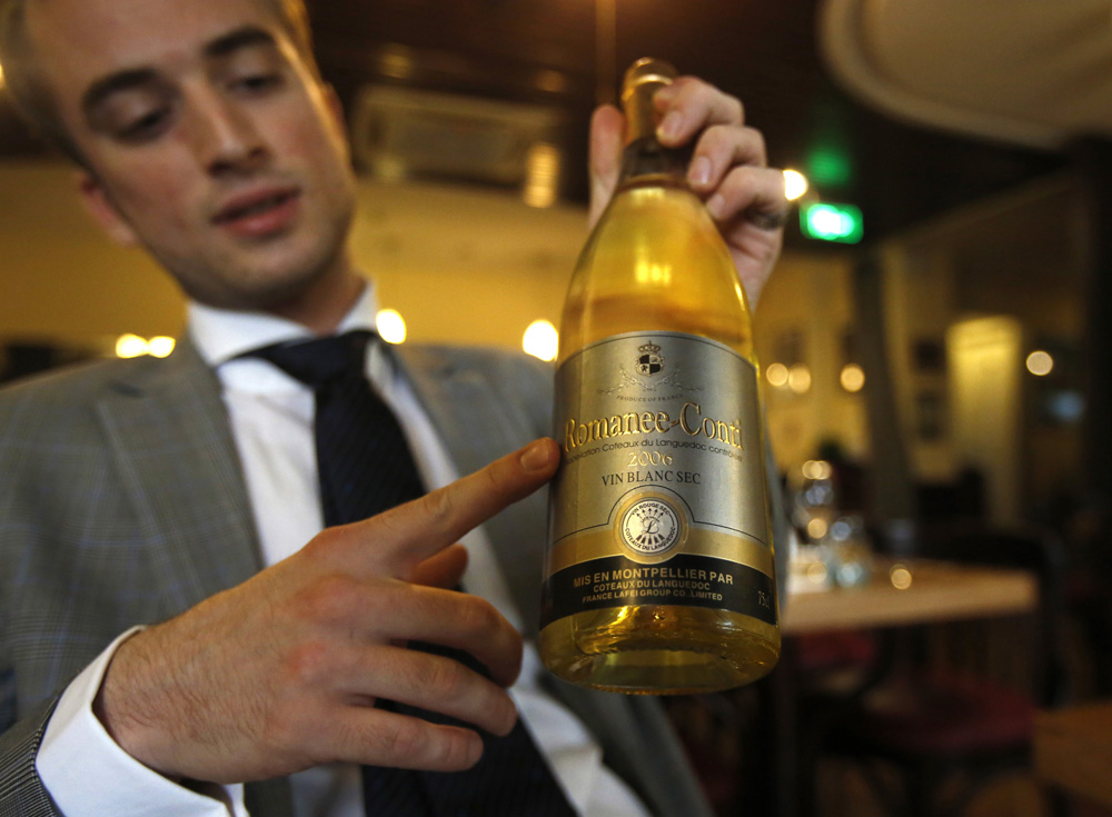 Gaudfroy shows a bottle of fake Romanee-Conti during a photo opportunity for Reuters in Beijing