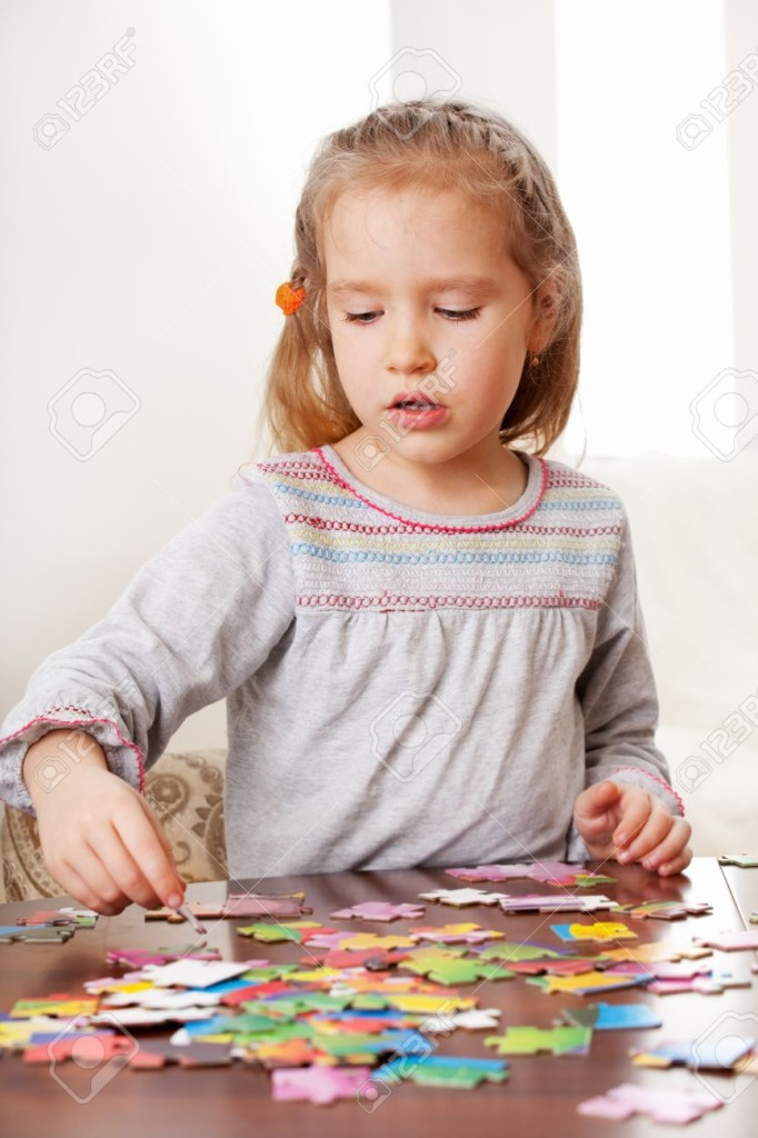 13472637-Child-playing-puzzle-Little-girl-play-at-home-Stock-Photo-puzzle-children-small